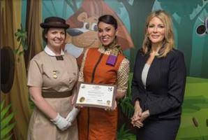 Linda Celestino, vicepresidenta de Experiencias de los Clientes de Etihad Airways (derecha), presenta a la niñera a bordo número 2.000 de la aerolinea, la española Isabel Moya Guzmán (centro), un certificado hecho expresamente para la ocasión.