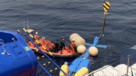 El helicóptero una vez izado del fondo, a la espera de subirlo al buque de Salvamento Marítimo.