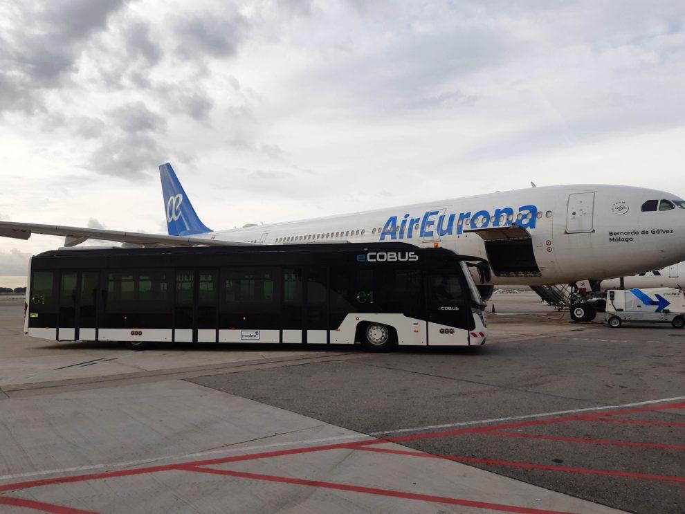El autobus eléctrico de Groundforce en el aeropuerto de Barcelona El Prat junto a uno de los Airbus A330 de Air Europa.