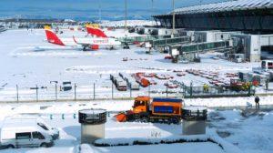 Barajas cubierto de nieve y una máquina quitanieves actuando en un parking de vehículos del aeropuerto.