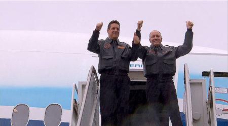 Van Chaney y Craig Bomben saludan desde la puerta del avión al llegar al estacionamiento tras el vuelo.