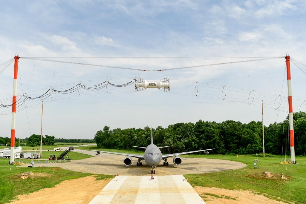 El Boeing KC-46 durante las pruebas de compatibilidad electromagnética en Patuxent River. Sobre él la bobina y transformador encargada de generar los pulsos electromagnéticos.