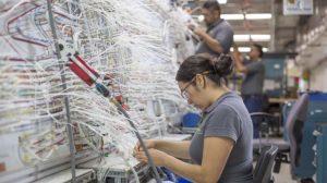 Empleados de Bombardier en Querétaro trabajando en el cableado de un avión.