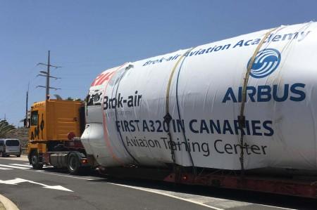 El fuselaje sobre el camión que le trasladó desde el puerto de Tenerife a las instalaciones de Brokair.