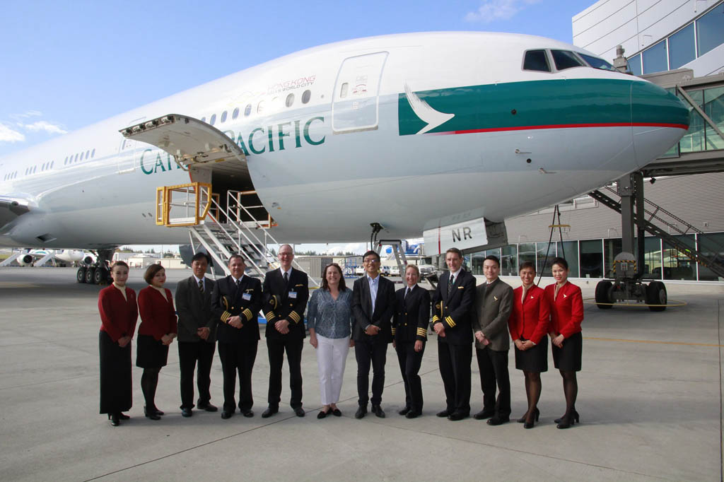 Directivos de Cathay Pacific y la tripulación del vuelo de entrega frente al Boeing 777 número 70 de la compañía.