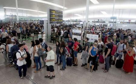 Cola de pasajeros a la espera de pasar el control de seguridad en el aeropuerto de Barcelona El Prat la pasada semana.