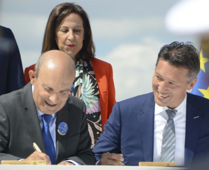 Firma en Le Bourget por parte de Eric Trapier de Dassault (izquierda) y Dirk Hoke de Airbus del acuerdo entre sus empresas para el desarrollo del FCAS. Entre ellos Margarita Robles, ministra de Defensa española.