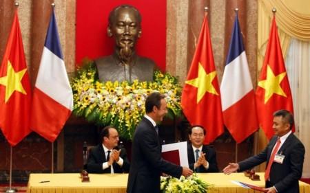 Los presidentes de Airbus (izquierda) y Vietnam Airlines se dan la mano tras la firma del acuerdo entre ambas empresas en presencia de los presidentes de Francia y Vietnam.