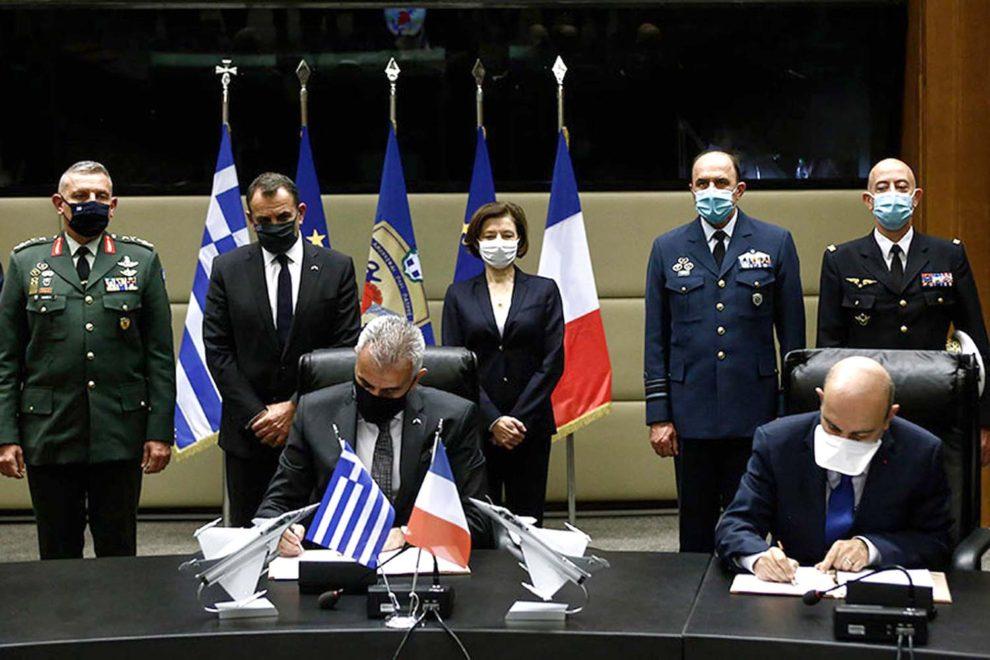 Theodoros Lagios, director general de Armamento e Inversiones del ministerio de Defensa griego y Eric Trappier, presidente de Dassault firman la comrpa de los Rafale.
