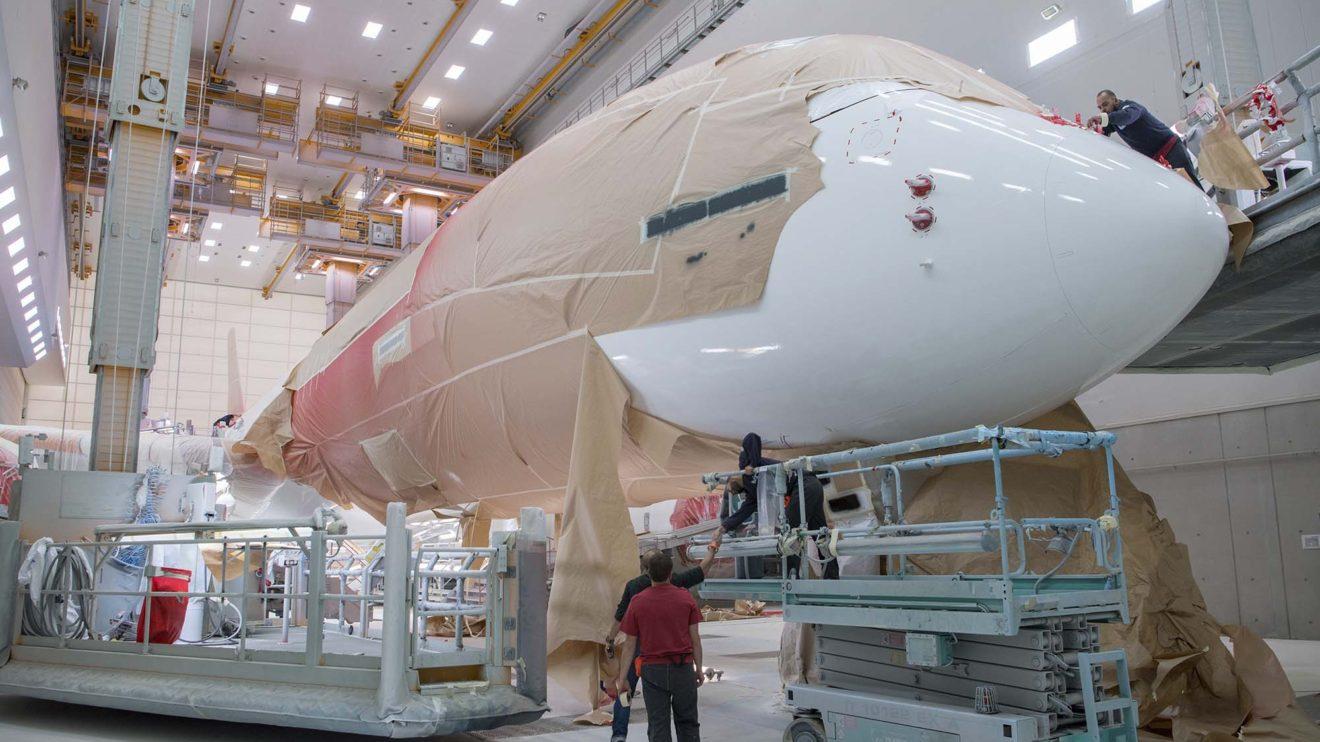 Un momento de la pintura del A350 EC´-MXV con gran parte del fuselaje enmascarado para aplicar la pintura roja.