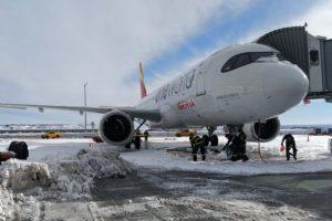 Retirada de nieve junto a un Airbus A320 de Iberia en la T4 del aeropuerto de Madrid Barajas.