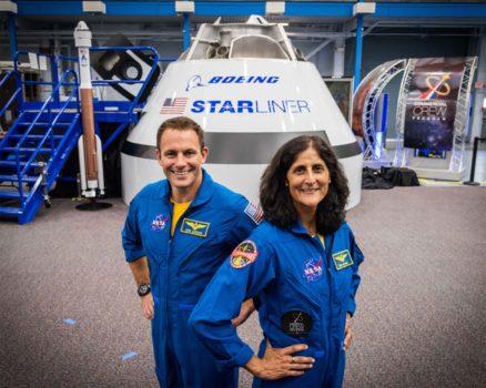Josh Cassada y Sunita Williams frente a un modelo de la cápsula Starliner.