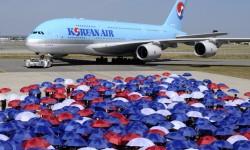 Algo más de un centenar de empleados de Airbus precedieron al A380 en su llegada al centro de entregas, con paraguas con los cuales después crearon el emblema de Korean Air.