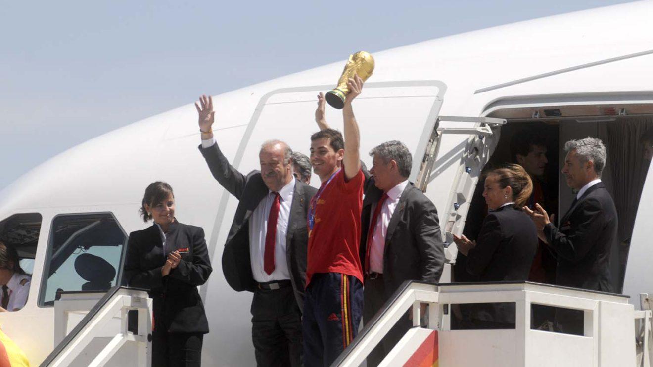 Iker Casillas, junto a Vicente del Bosque y Ángel María Villar saluda desde la puerta del A340 de Iberia, copa del mundo en alto, a la llegada de La Roja como campeona del mundo de fútbol.
