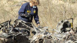Un miembro del equipo de investigación del NTSB examina los restos del helicóptero en el que falleció Kobe Bryant con su hija y otros seis acompañantes y el piloto.