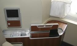 En un lateral del asiento de primera clase una mesa auxiliar, dos mandos para el sistema de entretenimiento y huecos para nuestros objetos personales