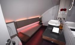 Los huecos a ambos lados de la escalera entre cubiertas en la superior han sido ocupados por Qatar Airways con unos lavabos para sus pasajeros de primera clase.