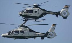 El EC135 y el AS365 de la Guardia Civil durante su pasada sobre la playa de Rota.