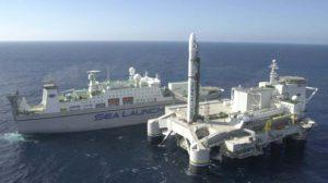 La plataforma Ocean Odyssey junto al buque de control, con un cohete Zenit 35L en posición de lanzamiento.