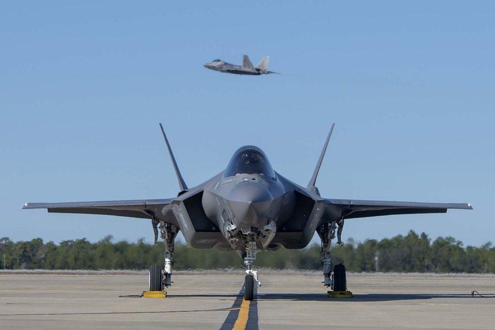 Un F-.35A rueda en la base aérea de Eglin mientras depsega un F-22.