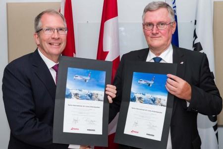 Rob Dewar de Bombardier y Peter Wojahn de Swiss celebrando la entrega del primer C Series.
